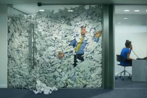 Image of man in office trapped by paperwork
